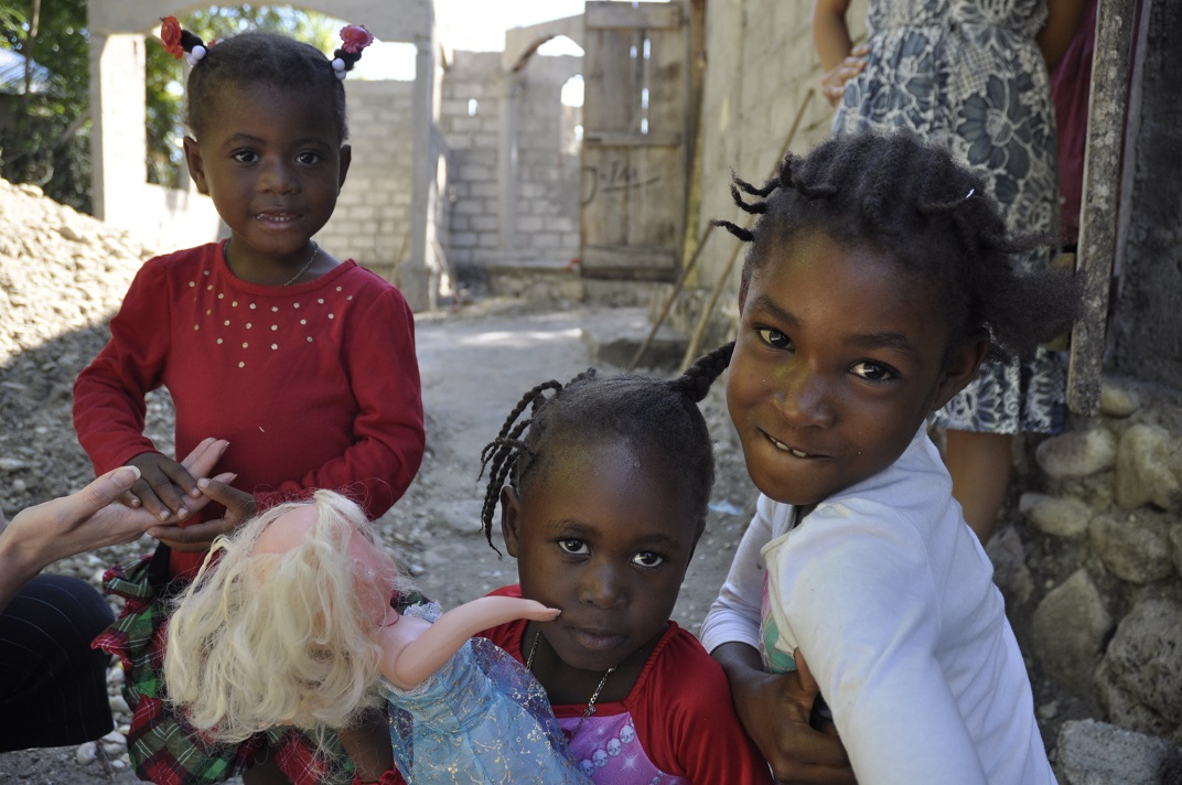 Little girls in Haiti playing with dolls