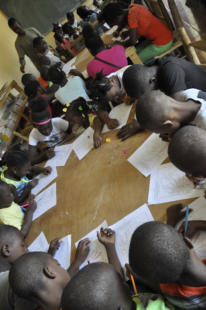 Haitian boys and girls crowd around tables to color at bible school