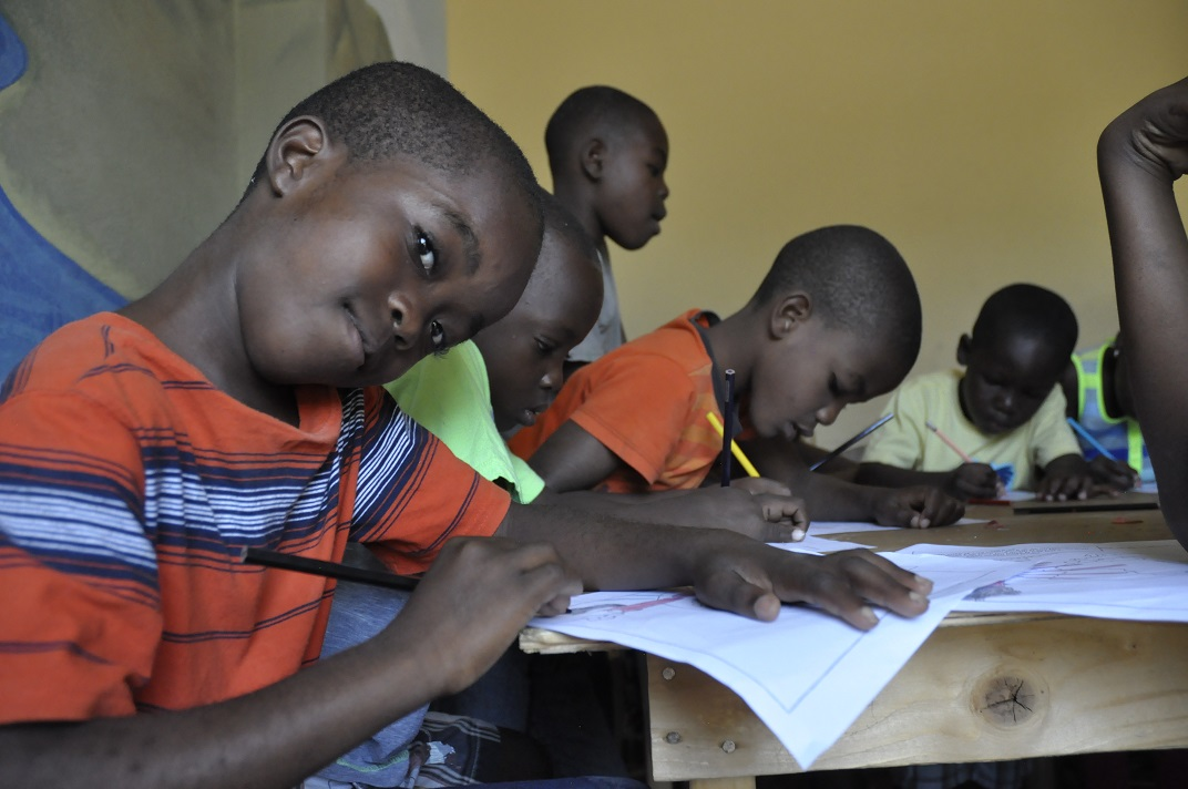 Haitian boy smiles for camera while coloring at his desk