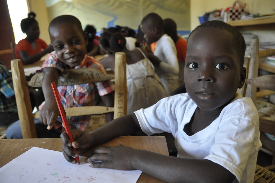 Haitian boy with big beautiful eyes poses for photo while coloring