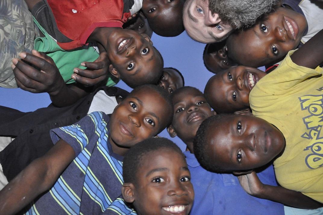 Haitian kids crowd around to look down on photographer