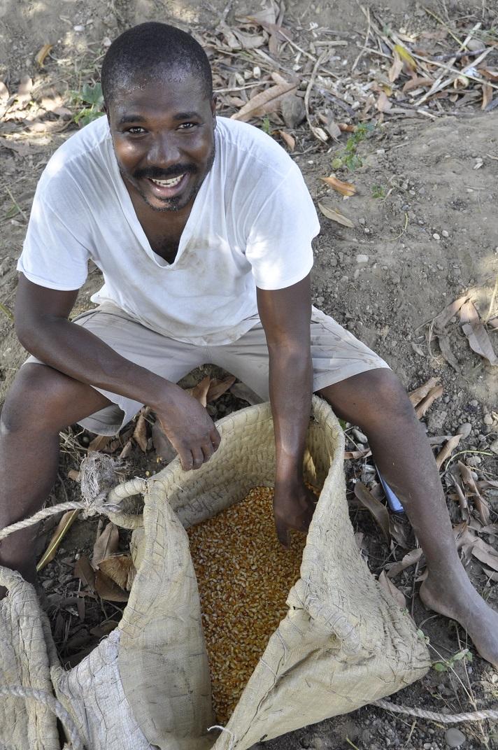 Haitian man with bag of corn seed