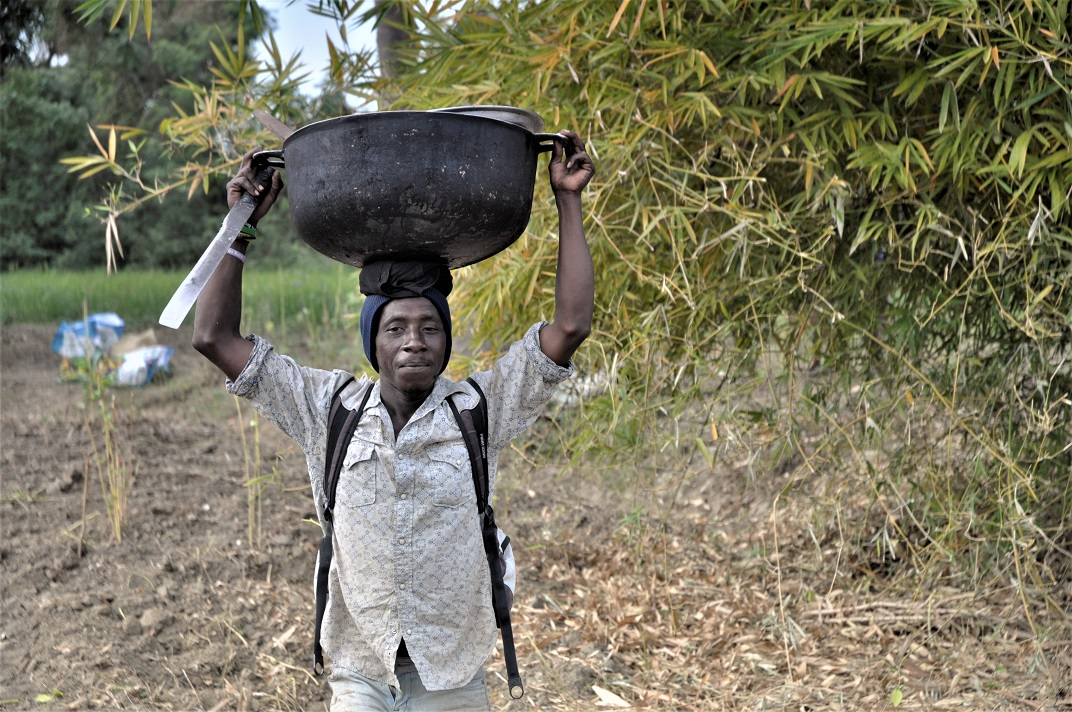 Haitian farmer carrying supplies home after working in field
