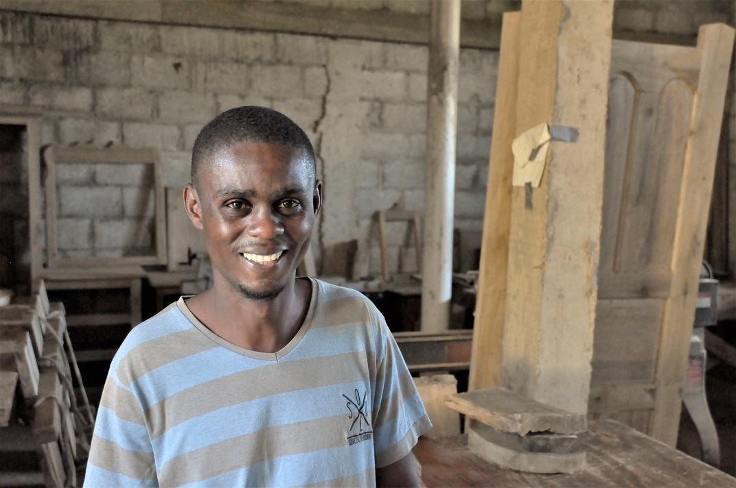 Haitian wood worker standing in wood working shop