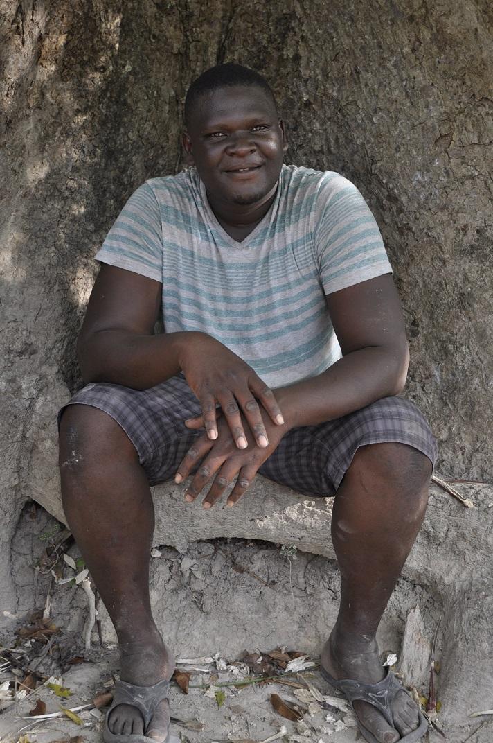 Beautiful Haitian man sits under tree