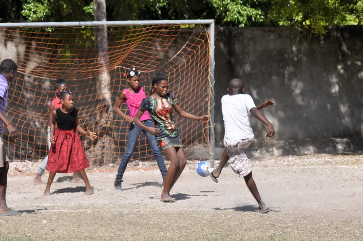 Haitian boy kicks soccer ball