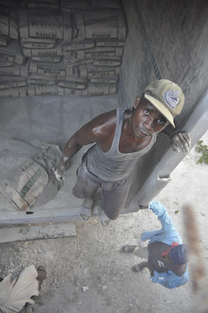 Haitian man unloads cement truck